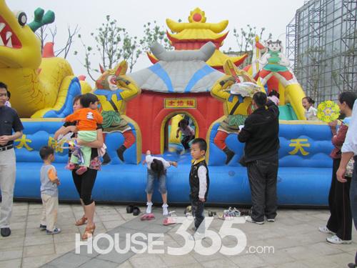 把各种颜色的气球编成可爱的动物形状,小朋友们围着小丑,稚嫩的小手伸
