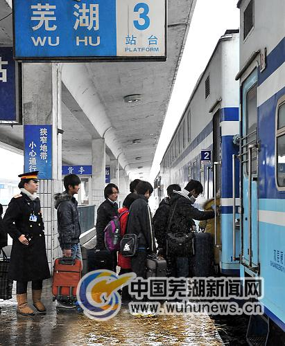 图为旅客在芜湖火车站踏着防滑草垫有序上车。